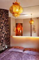 Mirrored wall above double bed with lilac bed linen, gold oriental pendant lamp and floral wallpaper on accent wall