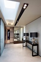 Classic lamps with chunky chrome bases on console table in minimalist atmosphere in corridor with designer components