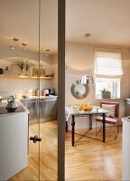 Interesting mixture of styles in kitchen-dining room; artistic table structure with metal struts, antique legs and glass top