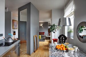 Grey kitchen counter with stainless steel fronts and dining table with floral pattern sandwiched in glass top; sculptural cupboard used as partition separating living area in background