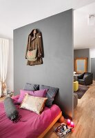 French bed with pink and grey textiles against partition wall screening living area