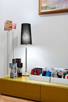 Collection of CDs, cube ornaments and table lamp on low sideboard