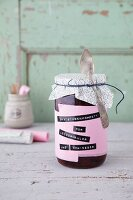 Damson compote in a jar labelled with black embossed band