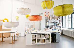 Pendant lamps with huge colourful slatted lampshades above desks in workshop
