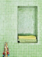 Bathroom with green mosaic tiles and towels in niche