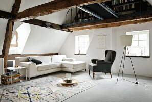Sofa, wing-back chair, classic side table and geometric rug below open-plan gallery