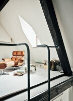Designer easy chair and footstool in gallery with dormer window and steel ladder