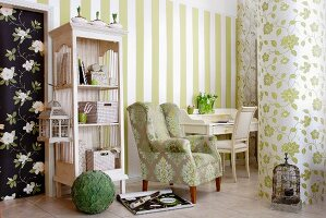 Traditional armchair with floral upholstery next to antique shelving unit painted white against walls covered with various patterns of wallpaper