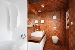 Mosaic wooden blocks covering walls, ceiling and floor in modern bathroom with washstand on base unit and wall-mounted toilet