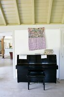 Black piano and bench in front of ethnic-style cloth bag hung on wall