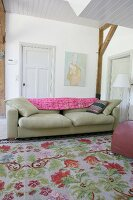 Vintage-style floral rug in front of sofa in rustic interior