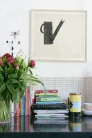 Stacked books on worksurface against tiled splashback below minimalist artwork on wall
