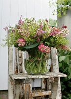 Glass vase of pink lupins on weathered wooden chair