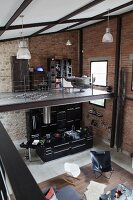 View from gallery down into loft interior with classic seating and open-plan black designer kitchen