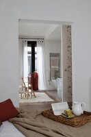 Cork tray on bed and view into ensuite bathroom through open doorway