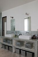 Masonry washstand covered in shiny silver mosaic tiles with twin countertop sinks in modern bathroom