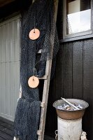 Fishing nets draped over ladder next to dish of seashells on cylindrical tub against house façade
