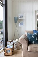 Scatter cushions on sofa, standard lamp and crate of magazines in corner of white, wood-clad living room