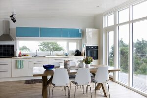 Pale kitchen counter and dining area with white chairs around wooden table in open-plan kitchen