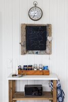 Box of spice jars on wooden shelving unit with white top below blackboard and station clock on white wooden wall