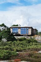Modern wooden summer house with large windows on slope