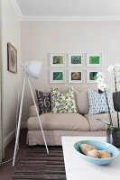Grey sofa with scatter cushions & tripod, studio-style lamp in modern living room