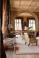 Antique side tables and armchairs with silk damask and ikat upholstery in grand salon with stucco ceiling and Tudor arch
