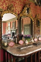 Gilt-framed triple mirror on sideboard with marble top in dining room with red and gold patterned wallpaper
