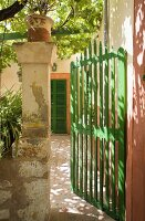 Green-painted gate and view of Mediterranean front door with ochre surround