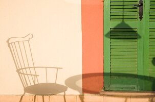 Shadow of chair and table on house façade next to green slatted door