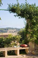 View from terrace past simple stone bench through trellis arch and across Mediterranean summer landscape