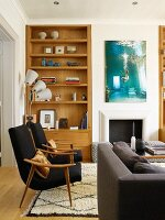 Fifties-style black armchairs with wooden frames in front of wooden fitted shelves in niche in living room