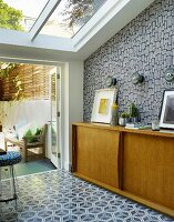 Fifties-style, pale wooden sideboard against patterned wallpaper and patterned tiled floor in front of terrace doors