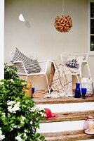 White mesh armchairs with cushions on narrow terrace with wooden steps and spherical rattan pendant lamp