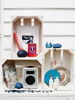 Bathroom utensils and maritime ornaments in stacked wooden crated against white wooden wall