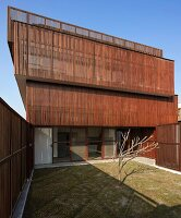 Austere courtyard of modern, Indian house with facade screened from sun by slim wooden slats
