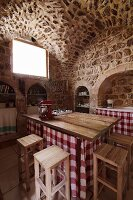 Kitchen counter with gingham-curtained base and wooden bar stools in old house with limestone walls and vaulted ceiling