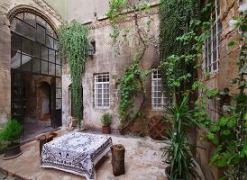 Large table with tablecloth in courtyard of old house with climber-covered walls and glass and steel door in arched doorway