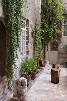 Courtyard of historic house with ape sculpture and planters on floor against facade