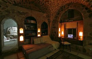 Lamps in living area with couch and work area in niche in old house with vaulted ceiling and limestone walls