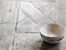 Three hand-crafted grey bowls on wooden surface