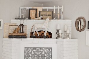Whitewashed brick fireplace decorated with animal figurines and silver candlesticks