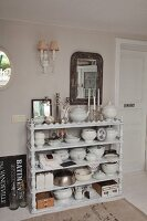 Collection of crockery on white wooden shelves with carved uprights against wall