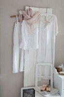 Nostalgische Kleider in Weiss an weiss lackiertem Holzpaneel vor pastellfarbener Wand