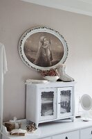 Small glass-fronted cabinet on chest of drawers below religious painting in oval frame on pastel grey wall