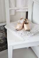 Vintage Ballettschuhe auf Spitzendeckchen und weiss lackiertem Küchenstuhl