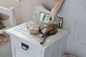 Haarbürste, Handspiegel und verschiedene Kristallgläser auf weiss lackiertem Nachttisch