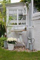 Vintage Waschschüssel und Krug in rostigem Metallgestell, weisse Hortensien im Zuber vor Gartenhäuschen