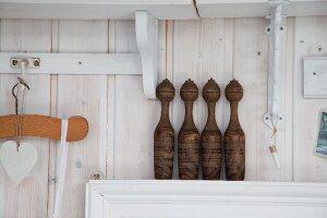 Alte Holz Kegel auf schmaler Ablage vor weiss lasierter Holzwand