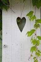 Weiss gestrichene Holztür mit herzförmigem Ausschnitt